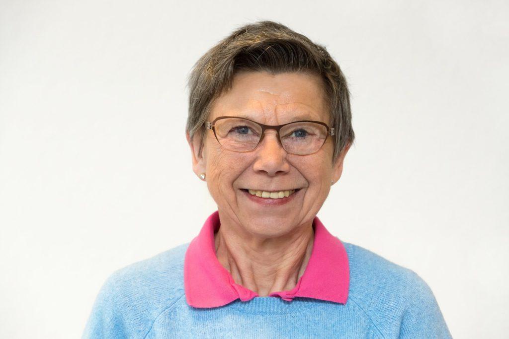 Frau mit Brille und blauem Pullover